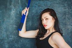 Portret mooie atletische vrouw met blauwe riem Vechtsportenconcept Binnen, studioschot Reeks op een grijze achtergrond stock afbeelding