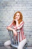 Portret Mooie jonge studente met rood krullend haar en sproeten op haar gezichtszitting op een houten stoel op een bakstenen muur royalty-vrije stock foto's