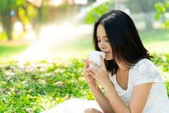 Portret Mooie meisje het drinken koffie in de tuin: Zij was royalty-vrije stock afbeelding