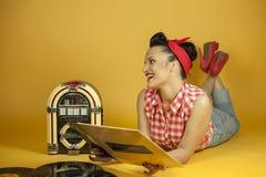 Portret mooie speld die omhoog aan muziek op een oude juke-box r luisteren stock fotografie