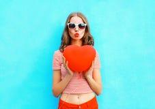 Portret mooie vrouw die luchtkus met de rode vorm van het ballonhart over blauw maken Royalty-vrije Stock Fotografie