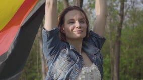 Portret mooie zekere vrouw die Duitse vlag in opgeheven op handen houden Vlag die in de wind fladderen Duitse burger stock videobeelden