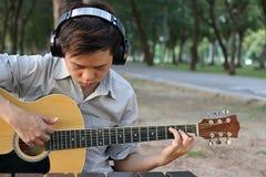 Portret muzyk lub gitarzysta bawić się gitarę akustyczną w zamazanej naturze z copyspace tłem obraz stock