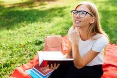Portret myślący dziewczyna uczeń z szkłami, siedzi na r zdjęcia royalty free