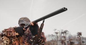 Portret myśliwy w łowieckim wyposażeniu celuje z strzału pistoletem, kłama w czekaniu w polu w zmierzchu świetle zdjęcie wideo