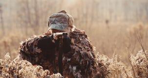 Portret myśliwy w łowieckim wyposażeniu celuje z strzału pistoletem, kłama w czekaniu w polu w zmierzchu świetle zbiory wideo