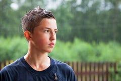 Portret nastolatek mężczyzny stojaki w deszczu i spojrzenia w odległość zdjęcia royalty free