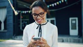 Portret nastoletni rozochocony amerykanin afrykańskiego pochodzenia używa smartphone outdoors ono uśmiecha się zbiory