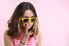 Portret nastoletnia dziewczyna mówi sekrety i plotki Tło menchie, studio zdjęcia royalty free