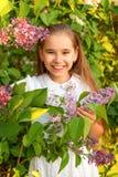 Portret nastoletnia dziewczyna z szeroko otwarty uśmiechem w lilych krzakach w białej sukni Obrazy Stock
