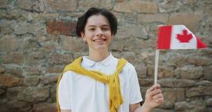 Portret nastoletniego chłopaka falowania kanadyjczyka flaga stoi outdoors ono uśmiecha się zbiory
