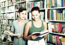 Portret nastoletniego chłopaka i dziewczyny klienci patrzeje otwartą książkę Fotografia Royalty Free