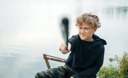 Portret nastoletniego chłopaka połów na banku jezioro lub rzeka Śliczna chłopiec z kędzierzawym włosy fotografia royalty free