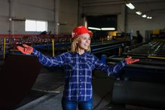 Metal tile manufacturing factory. Portret of nice beautiful woman in red safety helmet at metal tile roof manufacturing factory stock images