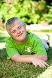 Portret niepełnosprawna chłopiec na zielonej trawie. Zdjęcia Royalty Free