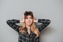 Portret nierada dziewczyna zakrywa jej ucho z rękami zdjęcie royalty free