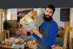 Portret niesie łozinowego kosz chleby przy kontuarem męski personel Zdjęcie Royalty Free