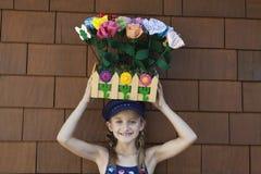 Portret niesie sztucznych kwiaty w drewnianej skrzynce na głowie mała dziewczynka fotografia stock