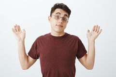 Portret niestaranny nieświadomy europejski męski coworker w round koszulce i szkłach, podnoszący palmy w poddaniu i udźwigu zdjęcie stock