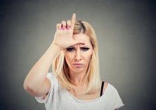Portret nieszczęśliwa kobieta daje nieudacznika znakowi na czole, patrzejący ciebie z złością i nienawiścią na twarzy obraz royalty free