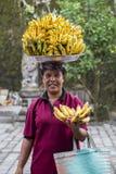 Portret niezidentyfikowana kobieta wraz z bananami na jej głowie na rynku wodną świątynią w Bali, Indonezja Obraz Stock
