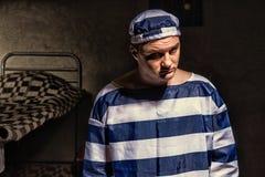 Portret nikczemny męski więzień jest ubranym więzienie jednolitą pozycję Zdjęcia Royalty Free