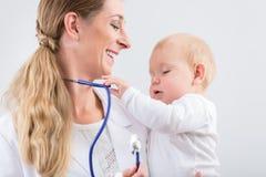 Portret oddany pediatryczny opieka specjalista ono uśmiecha się podczas gdy Fotografia Royalty Free