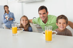 Portret ojciec i jego dzieci ma śniadanie Obrazy Stock