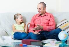 Portret ojciec i mała dziewczynka dyskutuje coś indoors Zdjęcie Royalty Free