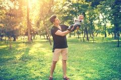Portret ojciec i syn ma zabawę w parku, ojca mienia dziecko, niemowlak Pojęcie rodzinny dzień w parku z młodymi rodzicami Zdjęcia Stock