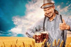 Portret Oktoberfest mężczyzna, będący ubranym tradycyjny Bawarskiego odziewa, słuzyć dużych piwnych kubki zdjęcia royalty free