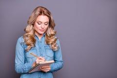 Portret ona ona ładna śliczna powabna atrakcyjna skupiająca się spokojna z włosami dama jest ubranym błękitną koszula pisze nowej fotografia stock