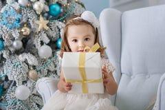 Portret ono uśmiecha się i trzyma śliczna mała dziewczynka boksuje z prezentami blisko choinki nowy rok, rąk lotniczych pojęcia a fotografia royalty free