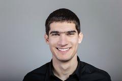 Portret ono uśmiecha się nad szarym tłem przystojny młody człowiek Fotografia Stock