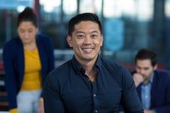 Portret ono uśmiecha się z kolegą pracuje w tle męski dyrektor wykonawczy Zdjęcie Stock