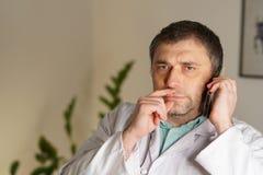 Portret opowiada na jego telefonie komórkowym pochłonięta lekarka obrazy stock
