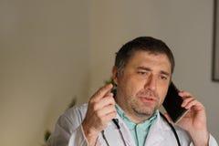 Portret opowiada na jego telefonie komórkowym pochłonięta lekarka fotografia royalty free
