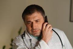 Portret opowiada na jego telefonie komórkowym pochłonięta lekarka obraz royalty free