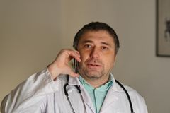 Portret opowiada na jego telefonie komórkowym pochłonięta lekarka obraz stock