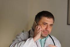 Portret opowiada na jego telefonie komórkowym pochłonięta lekarka fotografia stock