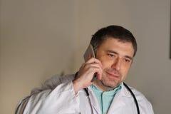 Portret opowiada na jego telefonie komórkowym pochłonięta lekarka zdjęcie stock
