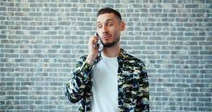 Portret opowiada na telefonie komórkowym ono uśmiecha się na ściany z cegieł tle radosny mężczyzna zdjęcie wideo