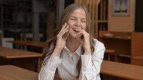 Portret opowiada na telefonie komórkowym rozochocona młoda kobieta zbiory