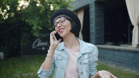 Portret opowiada na telefonie komórkowym stoi outdoors w mieście radosny uczeń zbiory