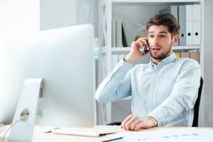Portret opowiada na telefonie komórkowym w biurze zdziwiony biznesmen Zdjęcia Royalty Free