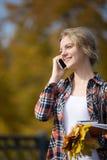Portret opowiada na telefonie młode uśmiechnięte studenckie strony zewnętrzne, Obraz Royalty Free