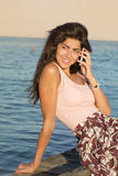 Portret opowiada na telefonie na plaży piękna młoda kobieta Obrazy Royalty Free