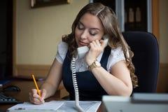 Portret opowiada na telefonie w biurze młody bizneswoman Zdjęcie Stock