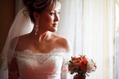 Portret panna młoda w profilu z ślubnym bukietem obok okno fotografia royalty free