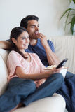Portret para ogląda TV podczas gdy jedzący popkorn Zdjęcia Stock